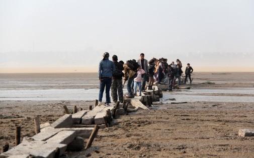 Des personnes marchent sur un pont séculaire traversant le lac, désormais asséché, de Poyang, en Chine, le 2 novembre 2013 Crédit : AFP