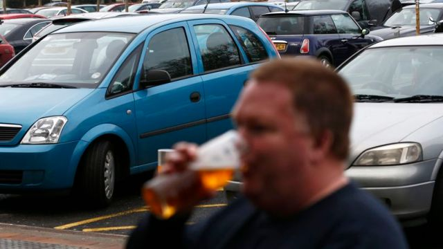 A man is seen drinking beer outside The Hope and Champion pub, located at the motorway services on the M40 near Beaconsfield