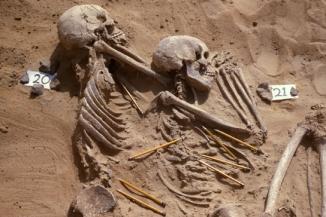 Une photo de deux victimes de mort violente. Les crayons pointent vers les fragments d'armes mêlés aux squelettes (Wendorf Archive, British Museum)