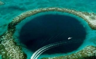 Ci-dessus, une photographie aérienne du Grand Trou Bleu, un gouffre sous-marin situé près des côtes d'Amérique centrale, dans lequel des analyses sédimentaires ont été réalisées afin d'éclaircir les raisons de la disparition de la civilisation Maya. Crédits : U.S. Geological Survey (USGS)